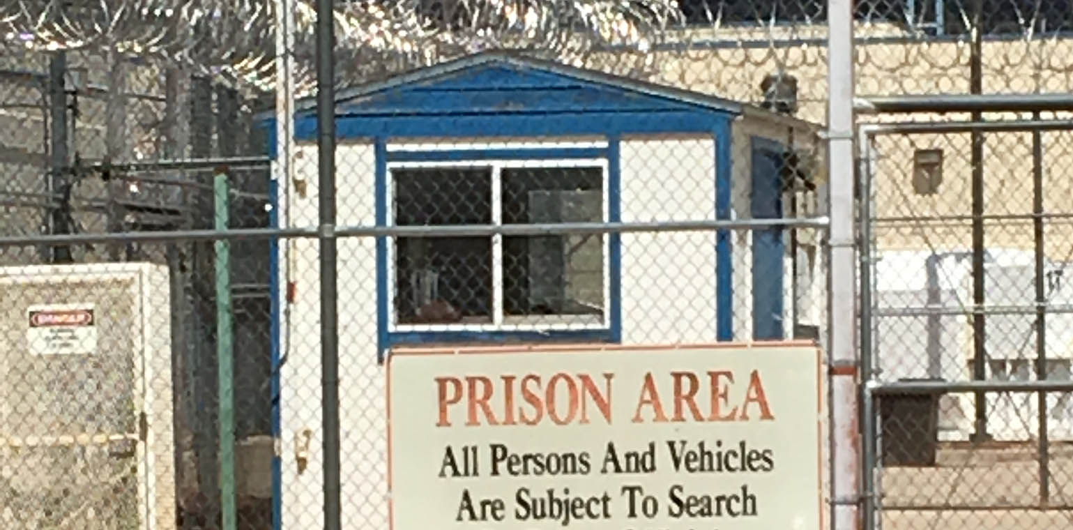 "Sign saying ""prison area"" on fence with barbed wire outside of jail"