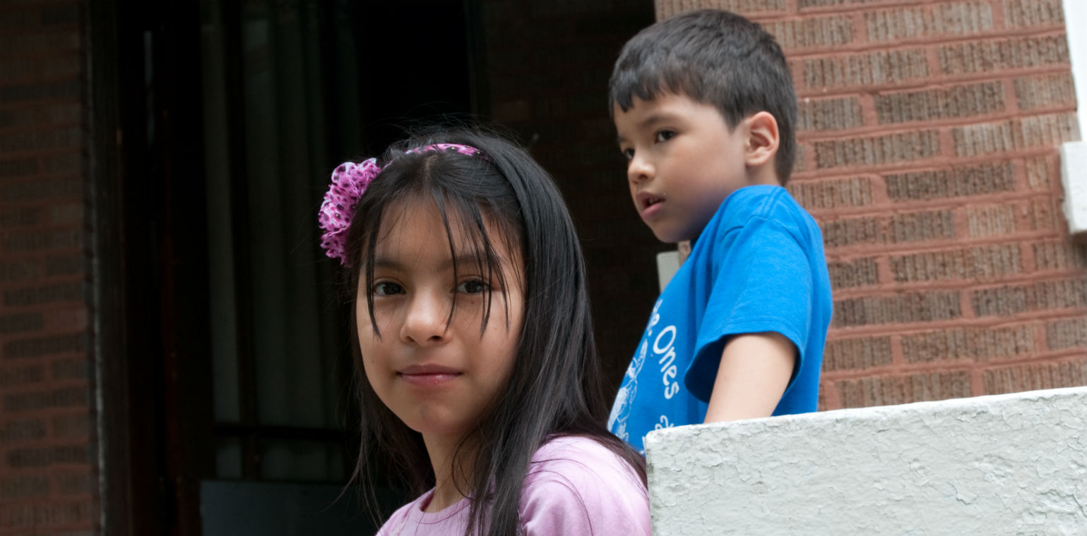 Young girl looking at camera with brother in background