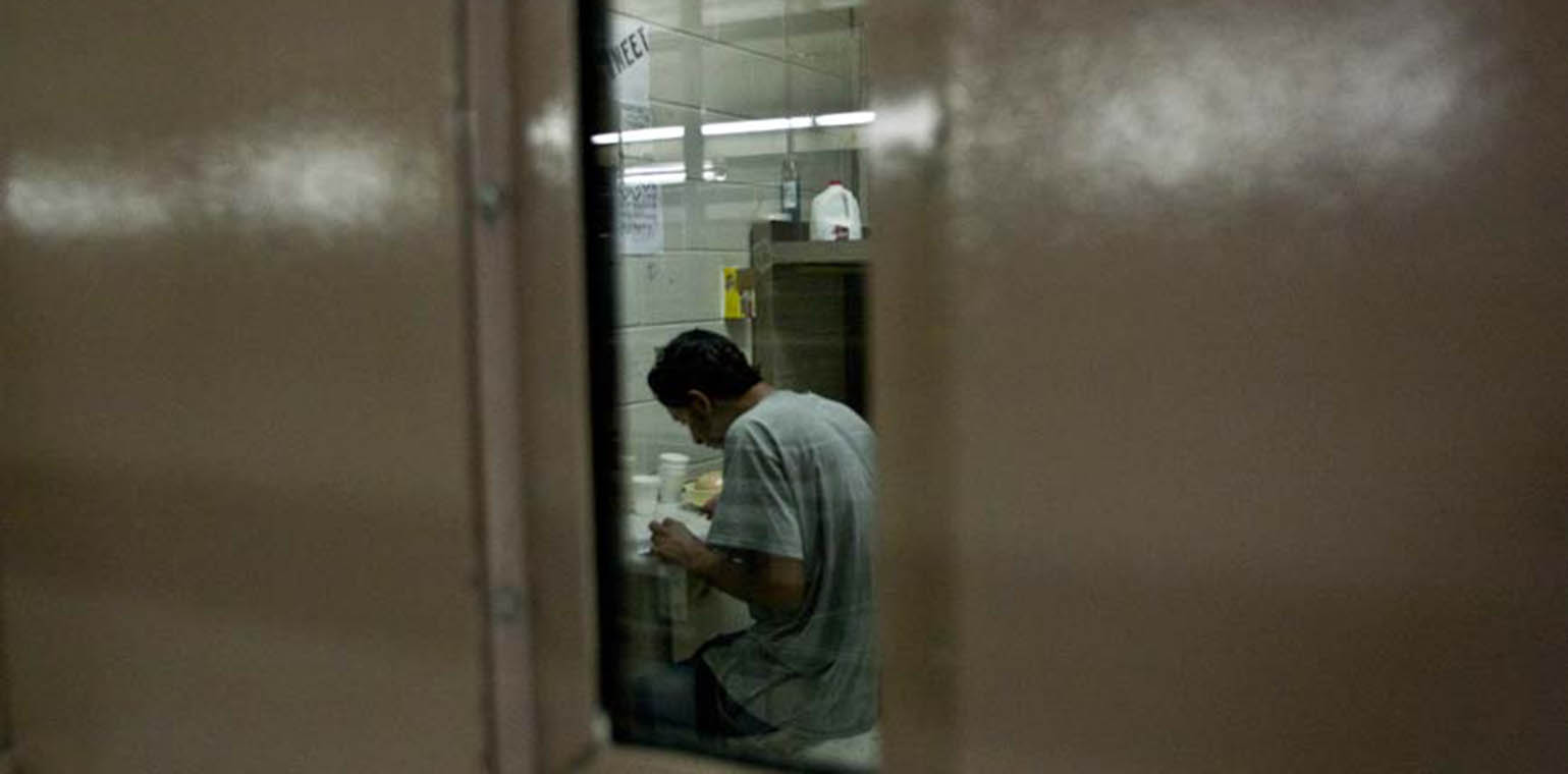 Looking in on person in a jail cell through a skinny window in cell door