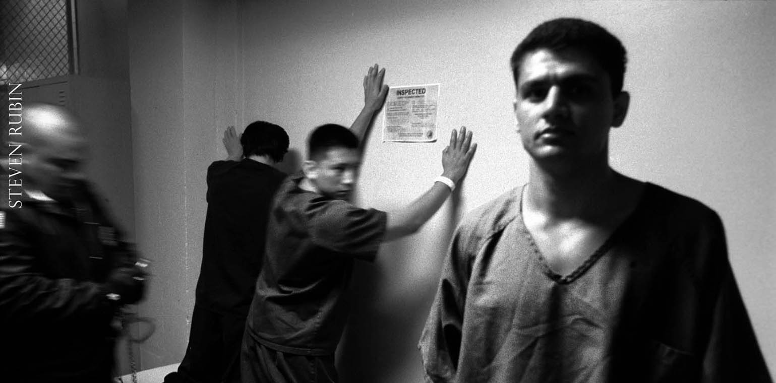 man in prison clothing, looking at the camera, other men against wall in background being searched by a guard. guard