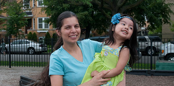 Woman holding young daughter and both smiling