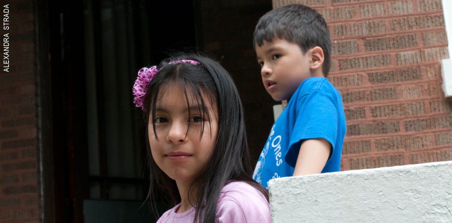 Young girl looking at camera with younger brother in background