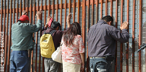 People facing the border wall with hands on the wall