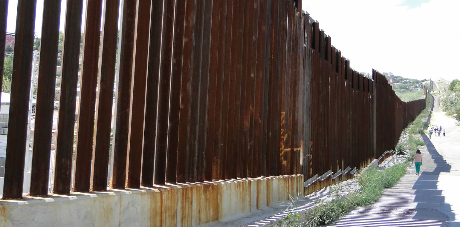 Steel slats of southern border wall extending far into the distance