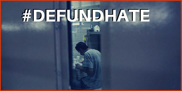 Picture of man in jail cell, looking through a skinny window, with overlaying text #DefundHate