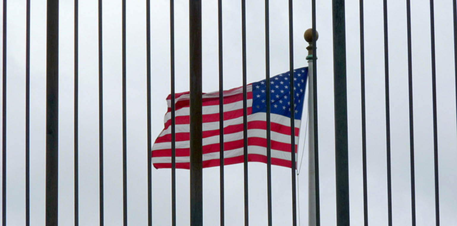 Photo of a U.S. flag flying to the left, with black iron fence bars in the foreground