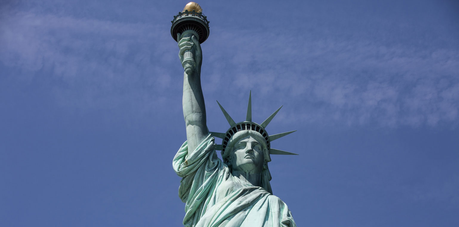 Photo of the Statue of Liberty against a backdrop of a blue sky.