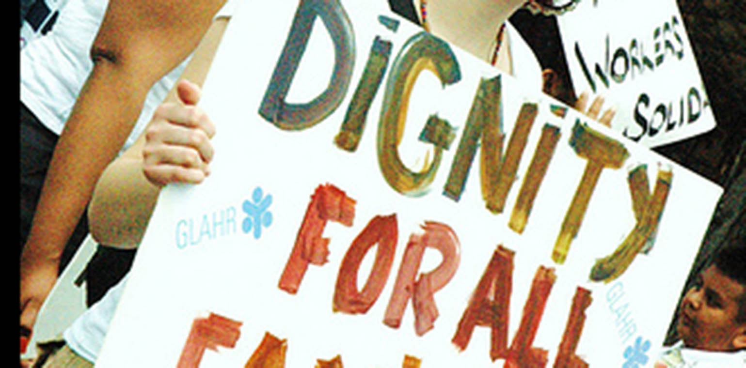 "Photo of a hand holding a protest sign that says ""Dignity for all"""