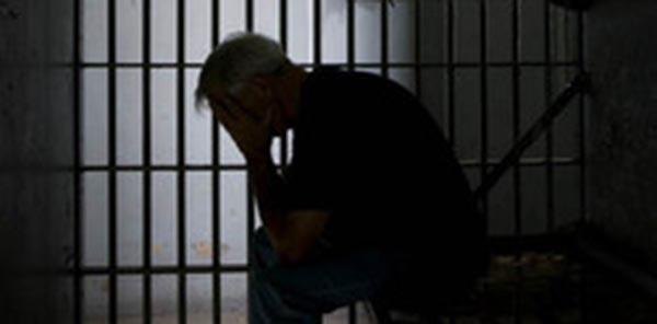 Silhouettee of a man sitting in a jail cell, holding his head in his hands, with cell bars behind him