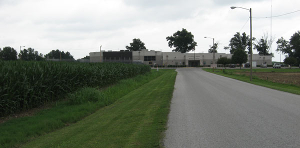 Photo of a road lined with corn fields leading to Pulaski County Detention Center in the distance
