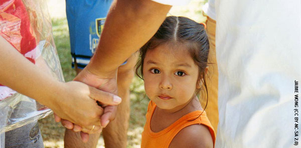 Photo of a young child looking at the camera. The forearms of two adults holding hands are in the foreground.