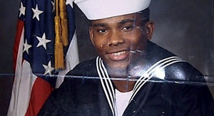 A photo of Howard Bailey in his Navy uniform, with a dark blue background and a U.S. flag behind him.