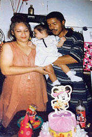 A photo of Leonel, his wife, and daughter, at a birthday celebration, with balloons behind them and a cake and gifts on a table in front of them