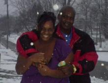 A photo of James and his wife outside, with their arms around each other, as snow falls around them
