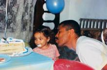 Photo of a father blowing out a candle on a birthday cake. Beside him is his young daughter, smiling, her mouth covered in frosting.
